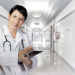 Royalty-Free Stock Photo: Brunette female doctor on duty at white hospital corridor, PHD
