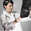 Brunette female doctor checking X-Rays - Stock Photo