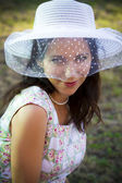 Sensual woman in the summer season with hat in a park — Stockfoto