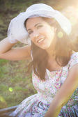 Happy woman in the park with hat under sunburst — Stock Photo