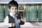 Criança vestida de homem de negócios sorrindo em frente ao prédio — Foto Stock