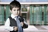 Enfant habillé homme d'affaires, souriant devant l'immeuble — Photo