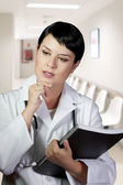 Thoughtful brunette female doctor on duty at the ER lobby — Stock Photo