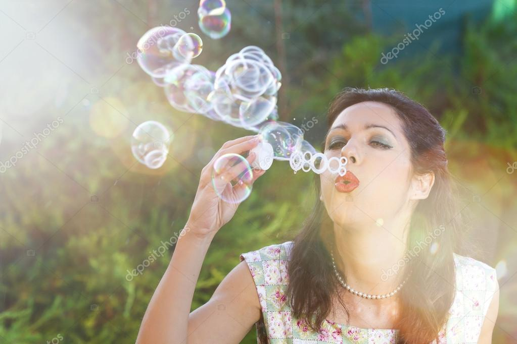 Romantic young woman inflating colorful soap bubbles in spring park — Stock Photo #12599592