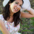 Beautiful woman in the summer season with hat in a park — Stock Photo