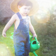 Little baby gardener concentrate in his work under sunburst — Stock Photo #13177742