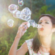 Romantic young woman inflating colorful soap bubbles in spring p - 图库照片