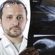 Doctor holding an x-ray appeal of a hand - Stockfoto