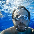 Man swimming underwater in the pool - Stock Photo