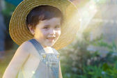 Little baby boy gardener smiling playful with sunburst — Stock Photo