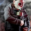 Police man with gas mask over explosion background - Stock Photo