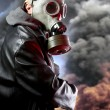 Armed man with gas mask over explosion background — Stock Photo