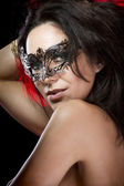 Sexy woman with venetian mask, red light at background — Stock Photo