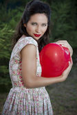 Valentine's Day. Beautiful smiling woman with a gift in the form — Foto de Stock