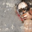 Portrait of beautiful woman over dirty wall with venetian mask — Stock Photo
