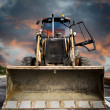 Stock Photo: Bulldozer, Yellow tractor on dramatic sky background