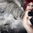 Sensual female angel posing over a cloudy sky with feathers — Foto de Stock