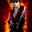 Stock Photo: Sexy brunette womin latex jumpsuit with heavy gun and helmet