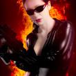 Stock Photo: Sexy brunette womin latex jumpsuit with heavy gun over fire b