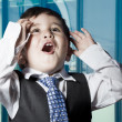 Child dressed businessman with funny face. surprise - Stock Photo