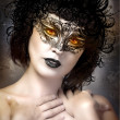 Young actress with venetian mask over fantasy background — Stockfoto