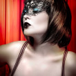 Young actress with venetimask over cabaret background — Stockfoto #21624147