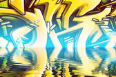 Graffiti reflection in the water, artistic yellow arrows — Stock Photo