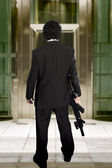 Man entering a business building with a machine gun — Stock Photo