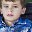 Blonde boy in sunny park looking at camera - Stock Photo