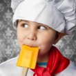 Little boy cook in uniform over vintage background playing wi — Stock Photo #23459862