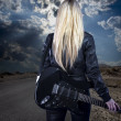 Beautiful young blonde dressed in black leather with electric gu — Stock Photo #23459876