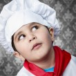 Happy boy cook in uniform over vintage background funny look — Stock Photo #23459902