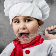 Little boy cook in uniform over vintage background — Stock Photo #23459948