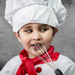 Little boy cook in uniform over vintage background playing with — Stock Photo #23459952