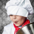Funny boy cook in uniform over vintage  background playing with - Stock Photo
