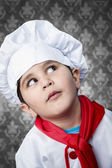 Happy boy cook in uniform over vintage background funny look — Stock Photo