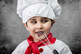 Little boy cook in uniform over vintage background playing with — Stock Photo