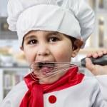 面白い少年は台所で料理のシェフに身を包んだ — ストック写真 #24048893