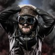 Pilot with glasses and vintage hat over background explosion — Stockfoto