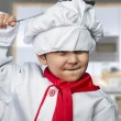 Funny child dressed as a cook with a pan hitting the head - Stock Photo