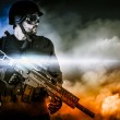 Stock Photo: Assault soldier with rifle on apocalyptic clouds