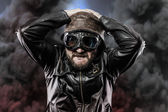 Pilot with glasses and vintage hat over background explosion — Stock Photo