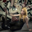 Young blonde holding a black guitar, over grafitti background — Stock Photo #25237623