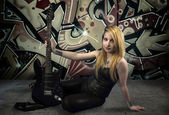 Young blonde holding a black guitar, over grafitti background — Stock Photo