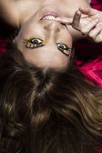 Mischievous beautiful woman lying on a red bed — Stock Photo