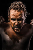 Anger man, Warrior young covered in mud — Stock Photo