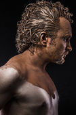 Man covered in mud, naked, in profile — Stock Photo
