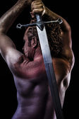 Warrior with big sword, muscular back — Stock Photo