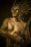 Combative, warrior or ancient god with golden mask and sword gre — Stock Photo