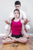 Par av idrottare i lotusställning med ljus — Stockfoto